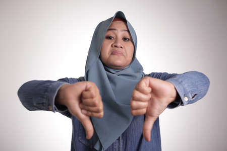 Portrait of muslim lady wearing hijab shows mocking face and thumbs down gesture, disappointed expression