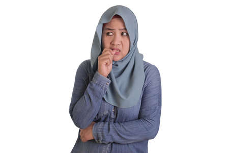 Portrait of Asian muslim woman wearing hijab looked worried and afraid of something bad, biting her nails, isolated on white