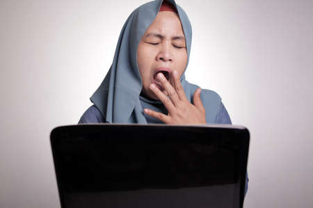 Portrait of Asian muslim woman tired for overworked and sleep in front of her laptop at the office 스톡 콘텐츠