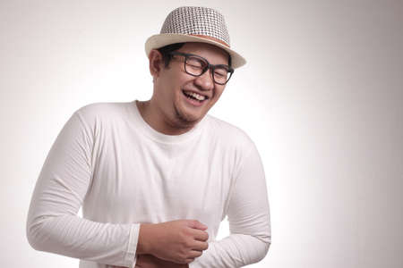 Portrait of funny young Asian man laughing hard with big open mouth, over white background 免版税图像