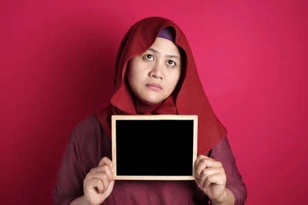 Portrait of Asian muslim woman wearing hijab holding and showing empty blackboard or chalk board with bad mood annoyed angry face, against red background, copy space