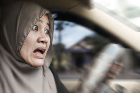Portrait of female Asian muslim driver shocked and panic about to have crash accident, zoomed motion blur defocus concept