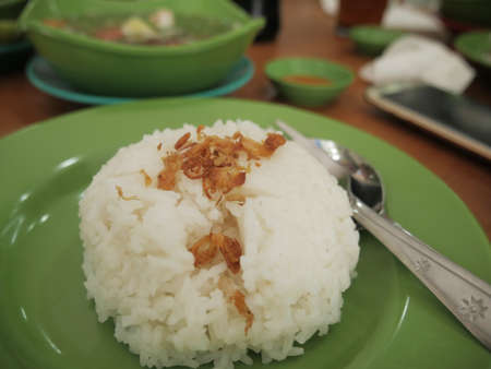 Close up of white rice on green plate served with a bowl of beef soup, ready to eat 스톡 콘텐츠