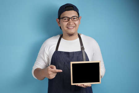 Portrait of Asian male chef or waiter looks happy and proud showing empty blackboard, presenting blank writing template, copy space meal menu concept