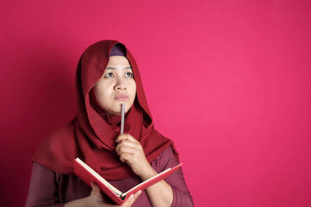 Happy confident successful Asian muslim woman wearing hijab  writing on book, smiling and thinking. Educational literacy or jurnalism concept Stock Photo