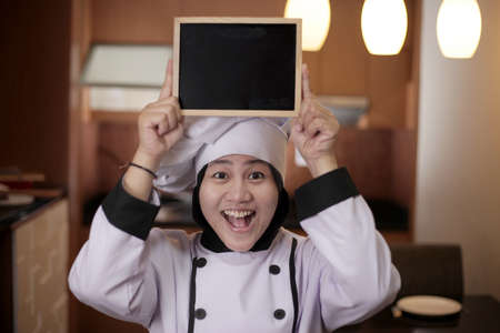 Portrait of Asian female chef looks happy and proud showing empty blackboard, presenting blank writing template, copy space meal menu concept Zdjęcie Seryjne