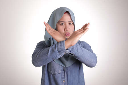 Portrait of muslim lady wearing hijab shows stop sign, prohibit forbid disallow something bad with crossed hand gesture