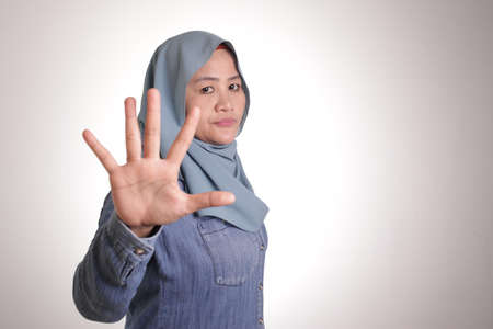 Portrait of muslim lady wearing hijab shows stop sign, prohibit forbid disallow something bad with palm hand gesture
