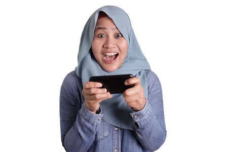 Happy Asian muslim woman excited to play games on her smart phone, isolated on white