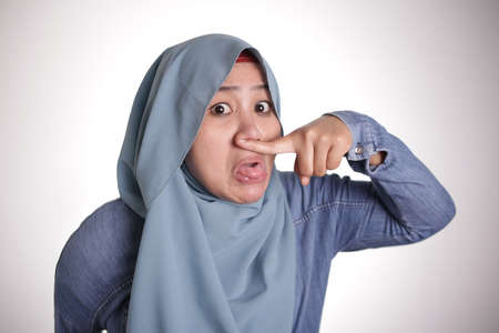 Portrait of cute funny Asian muslim lady wearing hijab close her nose because of bad disgusting smell odor Reklamní fotografie