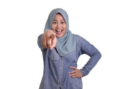 Portrait of Asian muslim lady wearing hijab pointing forward to camera as if choosing you gesture, business recruitment hiring concept