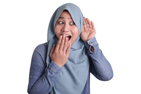 Portrait of Asian muslim woman smiling and doing hearing gesture, put hand on ear, listening carefully, isolated on white