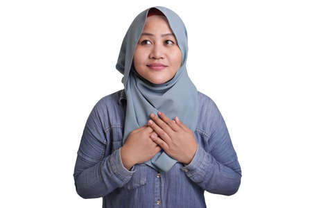 Portrait of muslim woman closing her eyes, smiling, hands on heart and pray