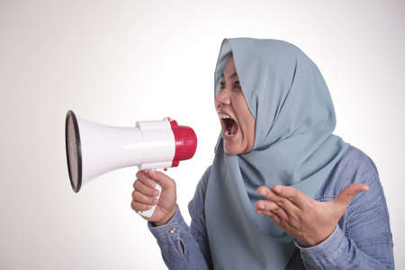 Young Asian muslim businesswoman wearing hijab screaming with angry expression on megaphone 免版税图像 - 140220574