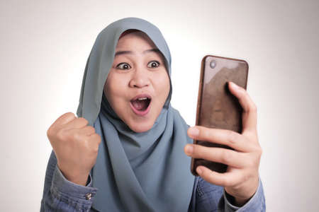 Portrait of young Asian muslim woman wearing hijab get good news on her phone, happy surprised expression Banco de Imagens