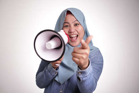 Portrait of Asian muslim woman with megaphone smiling and pointing forward, as if she is choosing you, job offer join us concept