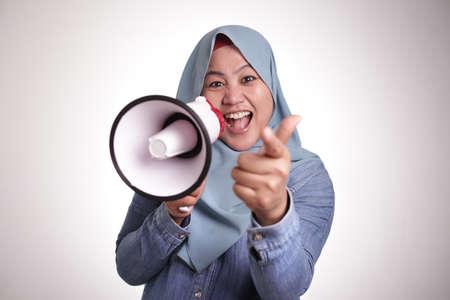 Retrato de mujer musulmana asiática con megáfono sonriendo y apuntando hacia adelante, como si te estuviera eligiendo, oferta de trabajo únete a nosotros concepto