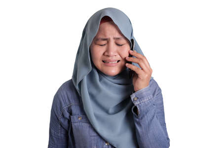 Portrait of Asian muslim woman get bad news on phone, sad crying expression. Isolated on white