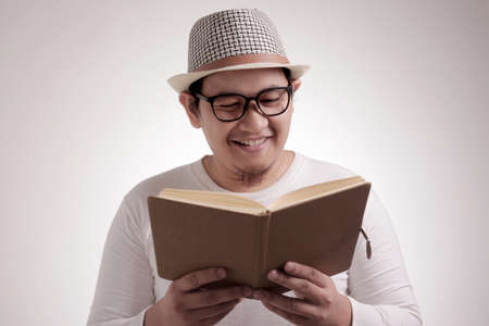 Portrait of Asian man wearing casual white shirt looked happy and smiling while reading a book