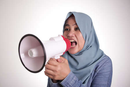Young Asian muslim businesswoman wearing hijab screaming with angry expression on megaphone