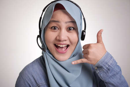 Portrait of beautiful young muslim lady wearing hijab, call center operator lady consultant smiling with headphones
