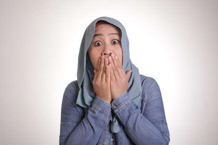 Portrait of Asian muslim woman wearing hijab closing her mouth with fingers. Worried gesture, can't say anything. Shocked surprised to hear bad news or gossip