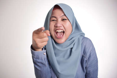 Portrait of muslim lady wearing hijab laughing hard and pointing forward, bully expression, close up head shot with selective focus