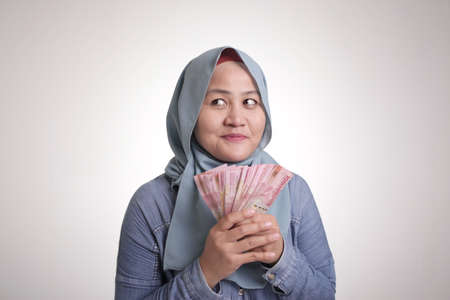 Portrait of Indonesian muslim woman holding rupiah money, smiling and thinking gesture
