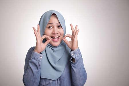 Porträt einer schönen asiatischen muslimischen Frau, die lächelt, während sie mit ihren Fingern eine köstliche Handgeste macht, isoliert auf weiß