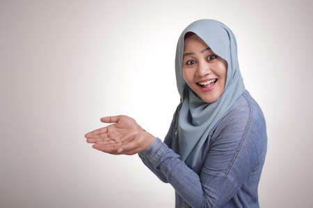 Portrait of Asian muslim lady wearing hijab smiling and shows something in her empty hands, presenting offering copy space template concept Imagens