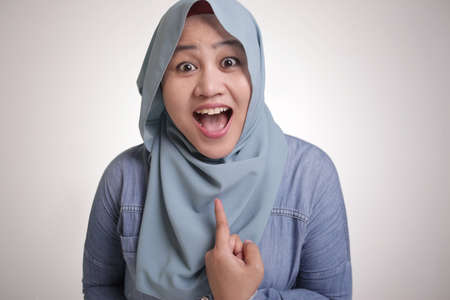 Portrait of confident muslim lady wearing hijab smiling and pointing at her self, isolated on white