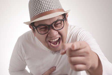 Portrait of funny Asian man laughing hard and pointing forward, bully expression, close up head shot with selective focus