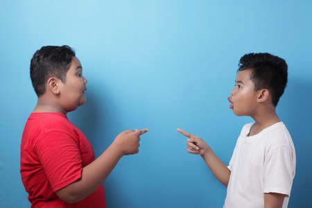 Two Asian boys screaming shouting at each other against blue background, little kids fight