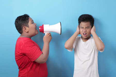 Big boy bullying small kid, school kid fight, student bully concept, screaming with megaphone