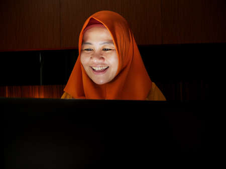 Asian Muslim women using hijab look surprised and happy to see good news received online in an email, women showing expressions of victory in front of her laptop 免版税图像