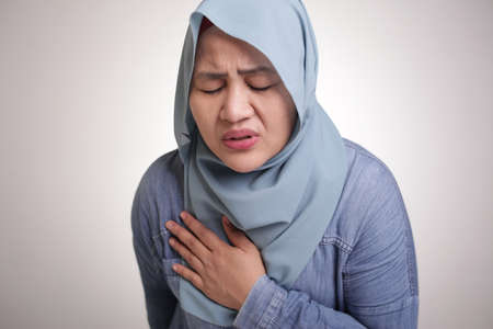 Portrait of muslim lady wearing  hijab having chest pain, heart attack concept