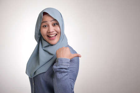 Portrait of Asian young happy muslim woman smiling and pointing to presenting something on her side, with copy space