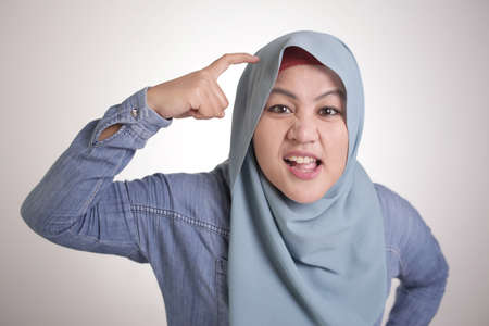Portrait of angry Asian muslim woman pointing head as if she is asking to use your brain or do you have brain concept