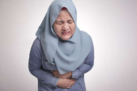 Portrait of Asian muslim woman suffer from stomach ache, health and medical concept