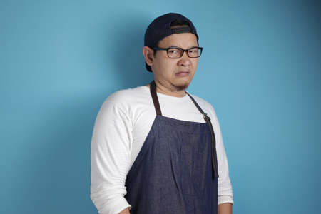 Portrait of young male Asian chef or waiter shows disgusted or displeased expression, refusal or rejection concept, against blue background Banque d'images