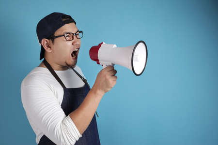 Portrait of funny young Asian male chef or waiter shouting with megaphone, mad yelling screaming crazy supporting motivating concept Standard-Bild