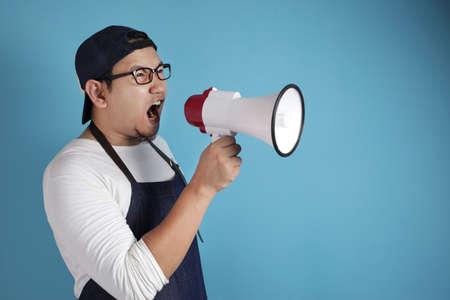 Retrato de divertido joven asiático chef o camarero gritando con megáfono, loco gritando gritando loco concepto motivador de apoyo Foto de archivo
