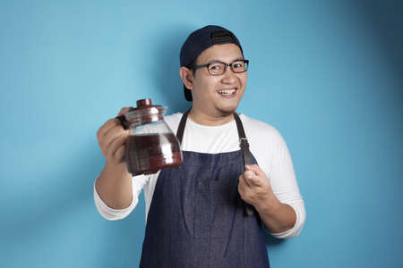 Portrait of Asian male chef or waiter smiling at camera while showing coffee pot, offering coffee concept, against blue background