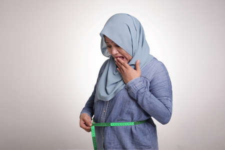 Portrait of funny fat Asian muslim woman shocked worried to see her big belly, measuring waist, obese concept 免版税图像
