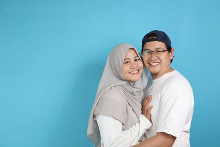 Portrait of happy Asian muslim couple smiling, husband and wife hugging full of love, family concept