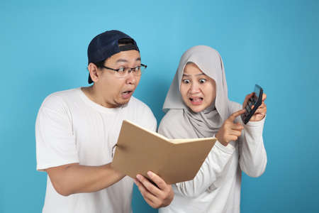 Portrait of Asian young muslim couple checking analyzing their family financial management report, young family housband and wife confused to have bad financial Banque d'images