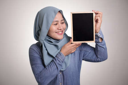Portrait of smart happy successful Asian muslim woman wearing hijab smiling at camera while holding and showing empty blackboard or chalk board with copy space 版權商用圖片