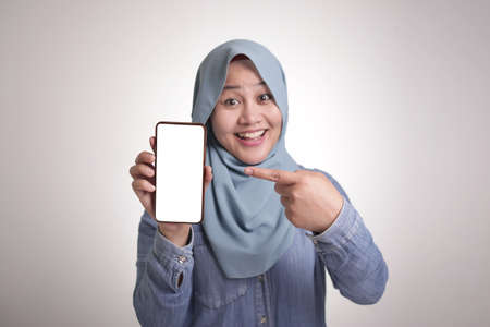 Portrait of Asian muslim woman looking at camera smiling and shows her smart phone, phone mock up, isolated on white