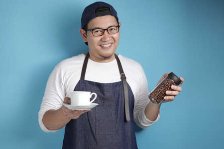 Portrait of Asian male chef or waiter smiling at camera while showing a glass of coffee, offering coffee beans concept, against blue background