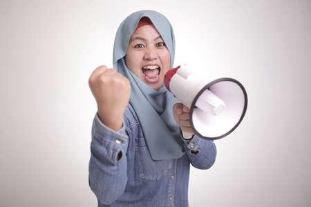 Jeune femme musulmane asiatique portant le hijab criant avec un mégaphone et pointant vers la caméra. Concept de partisan ou de manifestant de leader. Bouchent le portrait du corps